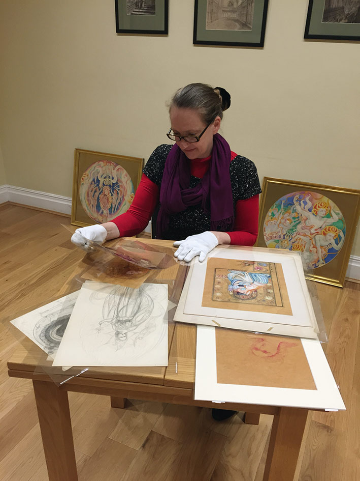Vivienne Roberts, curator, examines artwork as she prepares for the exhibition.